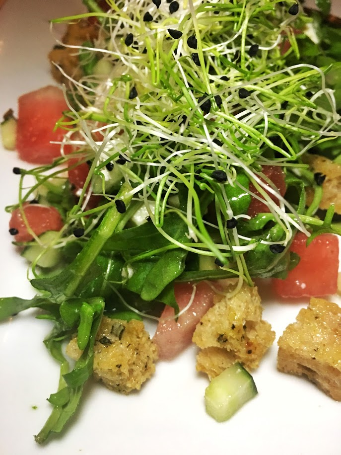 Watermelon Panzanella. Cubed local watermelon, cukes, feta cheese, herb croutons, arugula, onion sprouts with a shallot vinaigrette.